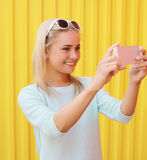 Happy smiling pretty girl makes self-portrait. Fashion, technology and people concept - happy smiling pretty girl makes self-portrait on the smartphone against Stock Photography