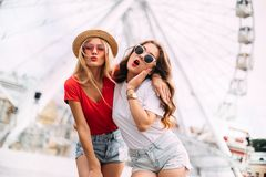 Happy smiling pretty girls having fun.stylishly dressed in short denim shorts and bright t-shirts, sunglasses. Posing on the background of a ferris wheel royalty free stock photos