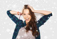 Happy smiling pretty teenage girl over snow. Winter, christmas, people, hair care and teens concept - happy smiling pretty teenage girl touching her head over Stock Photography