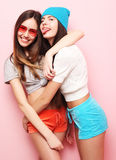Happy smiling pretty teenage girls or friends hugging over pink Royalty Free Stock Images