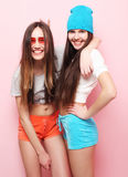 Happy smiling pretty teenage girls or friends hugging over pink Royalty Free Stock Photos