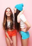 Happy smiling pretty teenage girls or friends hugging over pink Stock Photography