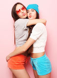 Happy smiling pretty teenage girls or friends hugging over pink Stock Images