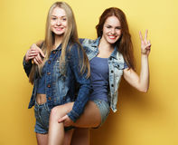 Happy smiling pretty teenage girls or friends hugging and showi. People, teens and friendship concept - happy smiling pretty teenage girls or friends hugging and Stock Photography