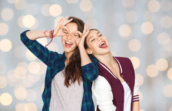 Happy smiling pretty teenage girls having fun. People, friends, teens and friendship concept - happy smiling pretty teenage girls having fun and making faces Royalty Free Stock Image