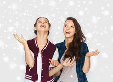 Happy smiling pretty teenage girls having fun. Winter, christmas, people and holidays concept - happy smiling pretty teenage girls or friends over gray Royalty Free Stock Photography
