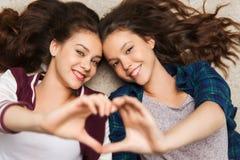 Happy smiling pretty teenage girls lying on floor Stock Photos