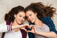 Happy smiling pretty teenage girls lying on floor Royalty Free Stock Images
