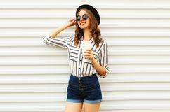 Happy smiling pretty woman with coffee cup in black round hat, shorts, white striped shirt on white wall. Background royalty free stock photos