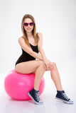 Happy smiling pretty young woman in sunglasses sitting on fitball Royalty Free Stock Image