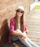 Happy smiling pretty young woman wearing a pink shirt and summer hat sitting resting in city Royalty Free Stock Photography
