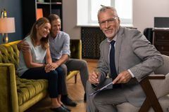 Happy smiling psychologist sitting next to his patients royalty free stock images