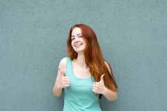 Happy smiling red-haired woman showing thumbs up royalty free stock photo