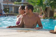 Happy smiling  while relaxing on the edge of a swimmingpool. Young couple   enjoying the sun in the swimming pool Royalty Free Stock Images