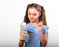 Happy smiling rich kid girl holding and count money on white bac. Kground with empty copy space Royalty Free Stock Images