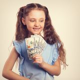Happy smiling rich kid girl holding money in the hand with natur. Al emotional face. Toned vintage portrait Stock Photo