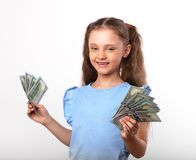 Happy smiling rich kid girl holding money in the hand with natur. Al emotional face on white background Stock Photos