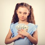 Happy smiling rich kid girl holding money and presseing to the c. Hest. Toned vintage portrait Stock Photography