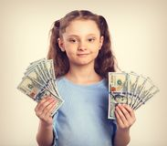 Happy smiling rich kid girl holding money in two hands with calm. Emotional face. Toned vintage portrait Royalty Free Stock Photos