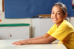 Happy smiling schoolgirl 10 in yellow at her desk Royalty Free Stock Image
