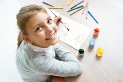 Happy smiling schoolgirl is drawing. Photo of a cute little girl doing homework. Education concept stock photos