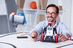 Happy smiling scientist making a selfy. What a moment Happy man in his forties taking pictures with a droid Stock Image