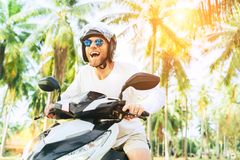 Happy smiling and screaming male tourist in helmet and sunglasses riding motorbike scooter during his tropical vacation under palm stock image