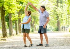 Portrait of a beautiful happy senior couple in love dancing in the park. Happy smiling senior couple in love, dancing and having fun in the park. Being together Royalty Free Stock Photography