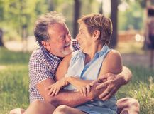 Portrait of a beautiful happy senior couple in love relaxing in the park. Happy smiling senior couple in love, relaxing, dancing and having fun in the park Royalty Free Stock Photography