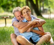 Portrait of a beautiful happy senior couple in love relaxing in the park Stock Photos