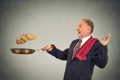 Happy smiling senior man tossing pancakes on frying pan Royalty Free Stock Photo