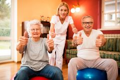 Happy smiling senior people with nurse shows finger up after success treatment royalty free stock images