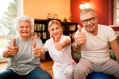 Happy smiling senior people with nurse shows finger up after success treatment stock photos