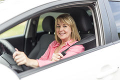 Happy and smiling senior woman in black car Stock Image