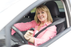 Happy and smiling senior woman in black car Stock Photography