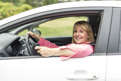 Happy and smiling senior woman in black car Royalty Free Stock Photo