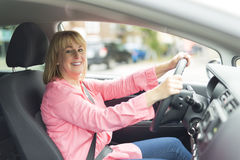 Happy and smiling senior woman in black car Stock Images