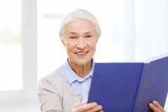 Happy smiling senior woman reading book at home. Age, leisure and people concept - happy smiling senior woman reading book at home Royalty Free Stock Photography