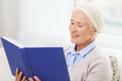 Happy smiling senior woman reading book at home Stock Photos