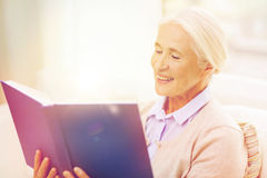 Happy smiling senior woman reading book at home Royalty Free Stock Photography