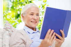 Happy smiling senior woman reading book at home Stock Image