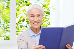 Happy smiling senior woman reading book at home Stock Images