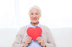 Happy smiling senior woman with red heart at home Royalty Free Stock Image