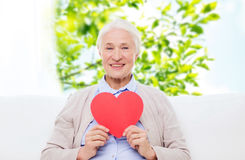 Happy smiling senior woman with red heart at home Royalty Free Stock Photography