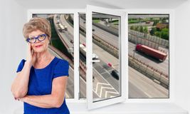 Happy smiling senior woman stands inside near threefold pvc window pane with hoisy highway with cars on background. Happy smiling senior woman standing inside Stock Photography