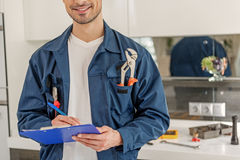 Happy smiling service man with map-case. Cheerful repairman is holding folder and pen. He standing at kitchen with smile Royalty Free Stock Images