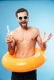 Happy smiling shirtless man wearing inflatable ring Stock Images