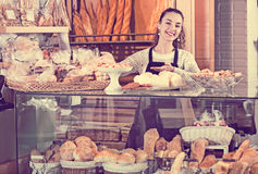 Happy smiling shopgirl working in bakery with bread Royalty Free Stock Images