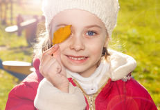 Happy smiling small girl holding a leaf outdoor during autumn Stock Image