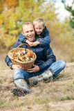 Happy smiling son and father with full basket of mashrooms Royalty Free Stock Photos